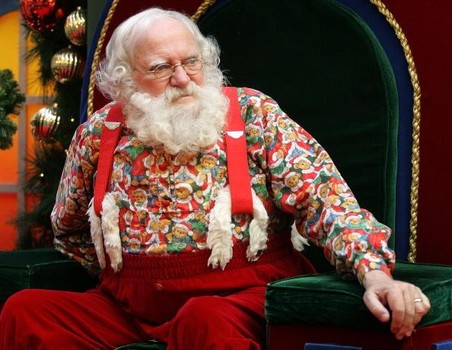 """NILES, IL - DECEMBER 21: Sporting a natural white beard, Santa Claus waits for the next child to sit with him at Golf Mill Shopping Mall December 21, 2004 in Niles, Illinois. This Santa calls himself a """"natural"""" Santa with real white hair and beard, and said children feel more comfortable when he is not wearing his traditional coat and hat. (Photo by Tim Boyle/Getty Images)"""